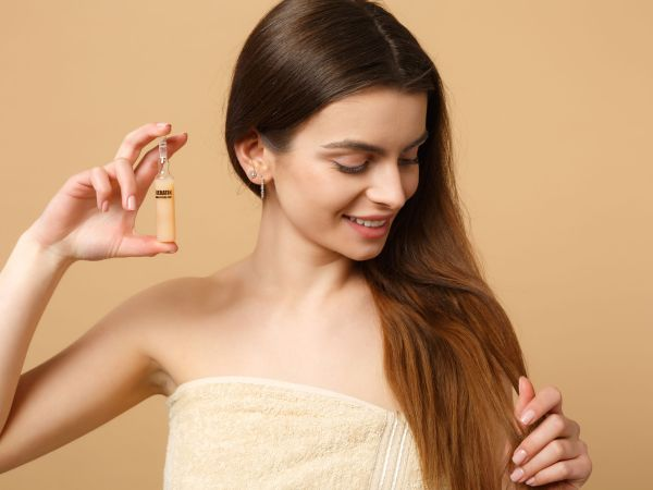 Mulher sorrindo enrolada na toalha segurando ampola de vidro.
