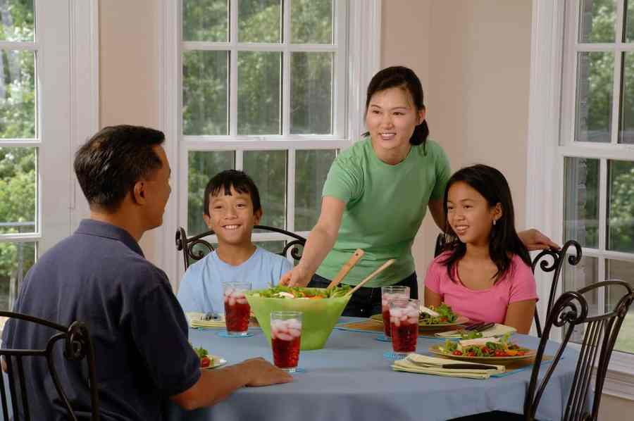 Imagem de uma família comendo à mesa em casa.