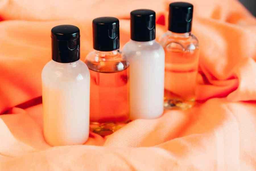 Quatro frascos preenchidos com cosméticos estão expostos em cima de uma toalha alaranjada.