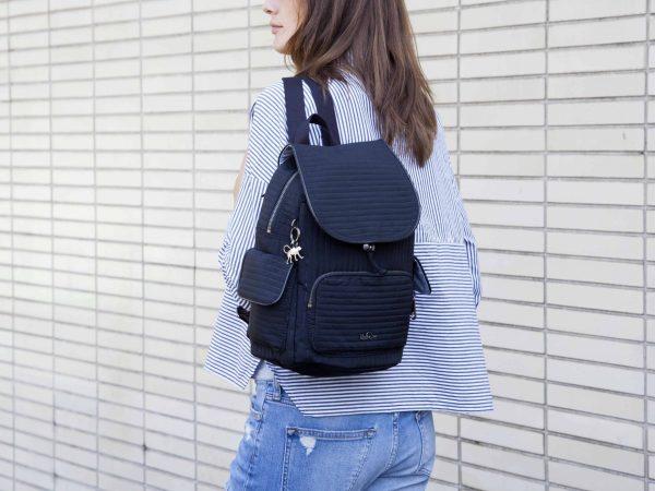 Imagem de uma moça usando uma mochila Kipling.