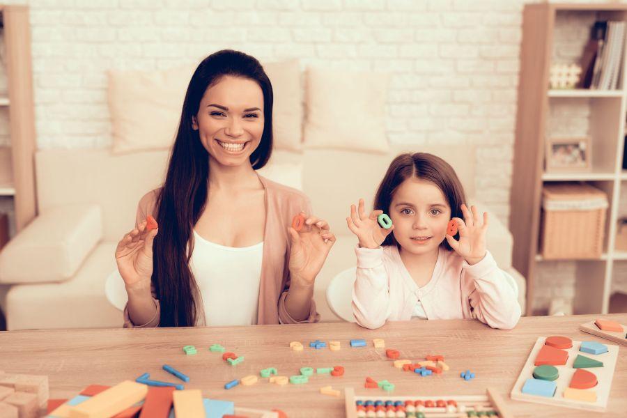 Mãe e filha segurando peças de jogo.