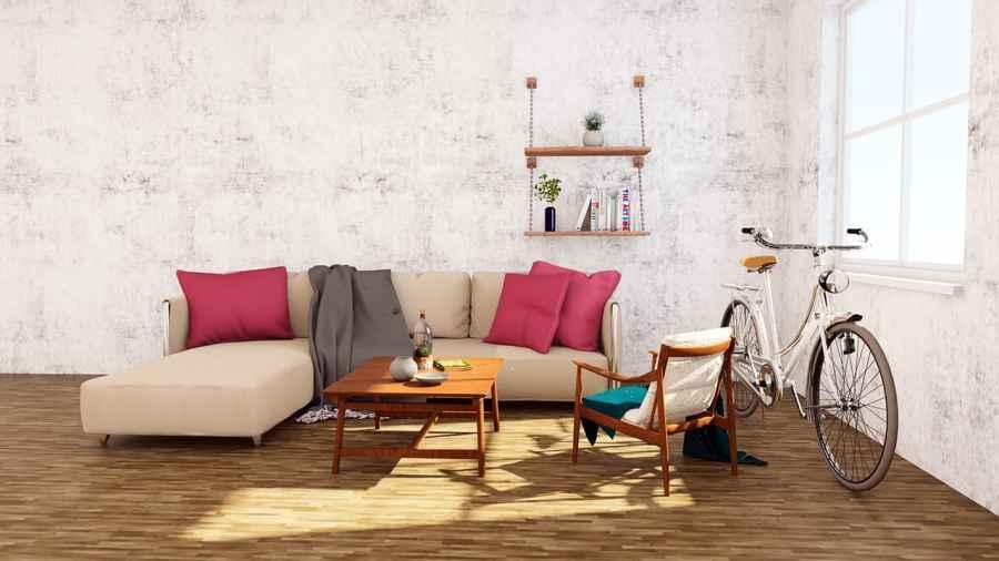 Na foto uma sala de estar com um sofá bege com almofadas rosas, uma bicicleta ao lado e uma mesa de centro em madeira na frente.