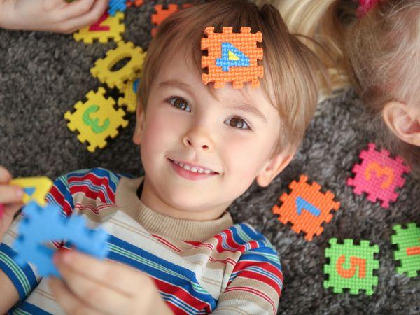 Na foto um menino deitado com uma peça de quebra-cabeça em sua cabeça.