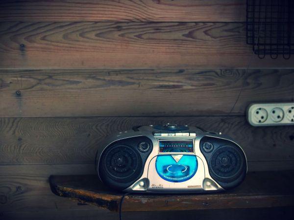 Imagem mostra um rádio portátil sobre uma mesa de madeira, em frente a uma parede de madeira com uma tomada fixada nela.