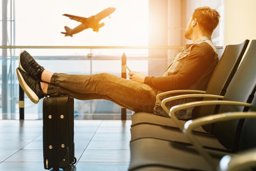 Homem sentado no aeroporto com avião ao fundo.