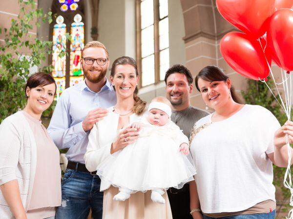 Na foto pais com um bebê e amigos ao redor segurando balões em formato de coração.