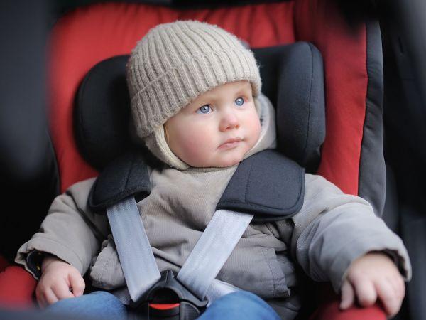 Bebê sentado em bebê conforto no carro.