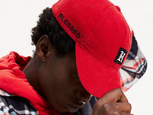 Um homem está de cabeça baixa, usando um boné que tampa parte de seu rosto e segurando a aba do acessório.