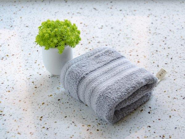 Toalha de rosto dobrada ao lado de vaso de planta