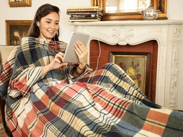 Na foto uma mulher sentada com um cobertor com mangas segurando um tablet.