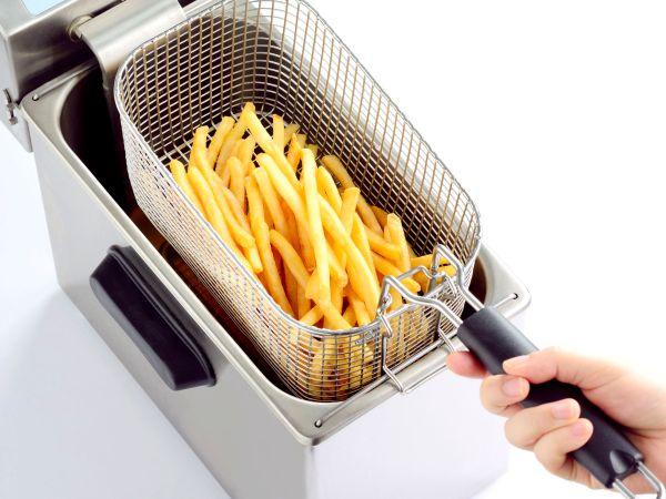 Mãos retirando cesta com batatas de fritadeira elétrica