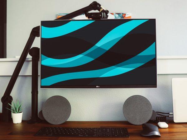 Imagem mostra um monitor LG preso por um suporte sobre uma mesa.