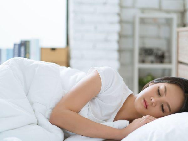Mulher dormindo em cama com roupas de cama brancas