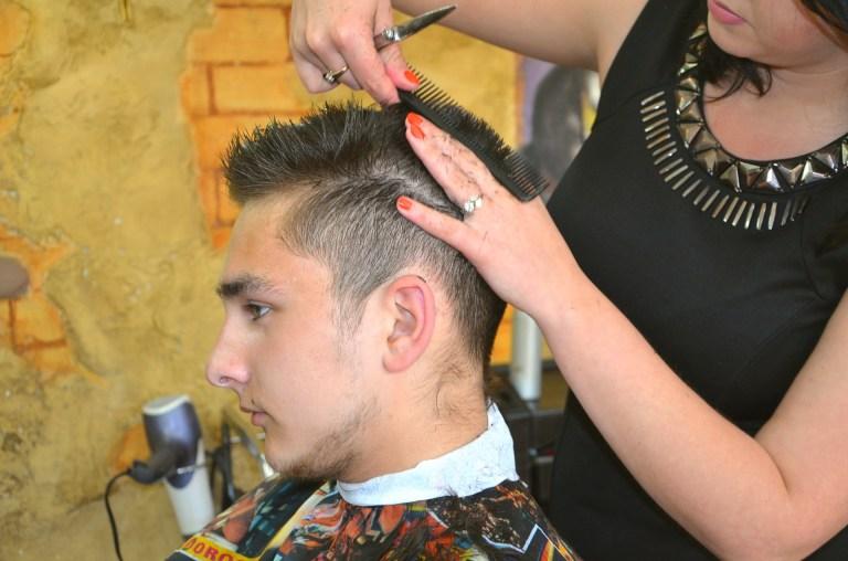 Imagem de homem cortando o cabelo em um salão com suporte para secador de cabelo ao fundo