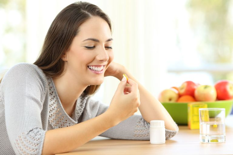 Mulher tomando um comprimido com maçãs ao fundo.