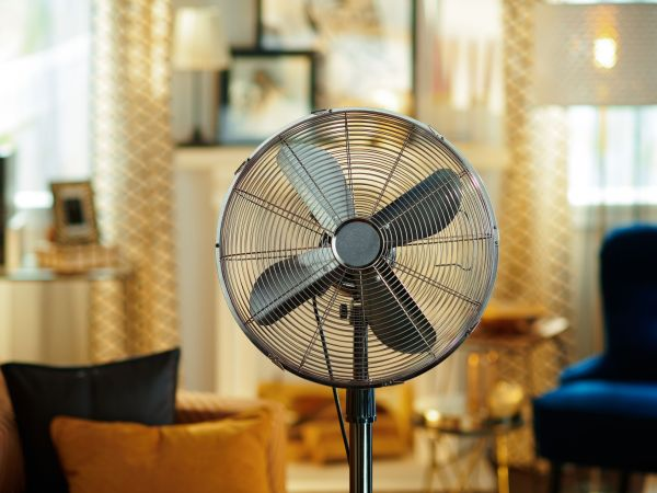 Closeup on electric floor standing fan in the modern living room in sunny hot summer day.