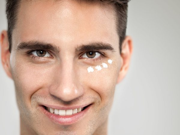 Portrait of young man with anti- aging cream, skincare