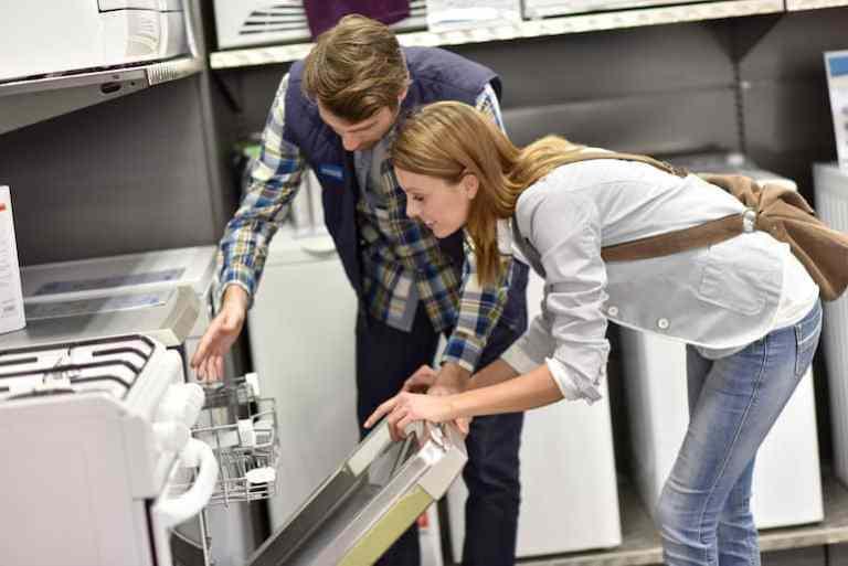 Donna che analizza una lavastoviglie in un negozio