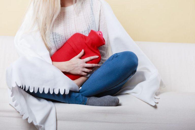 Donna con borsa dell'acqua calda rossa