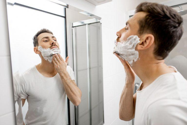 Uomo che si fa la barba allo specchio