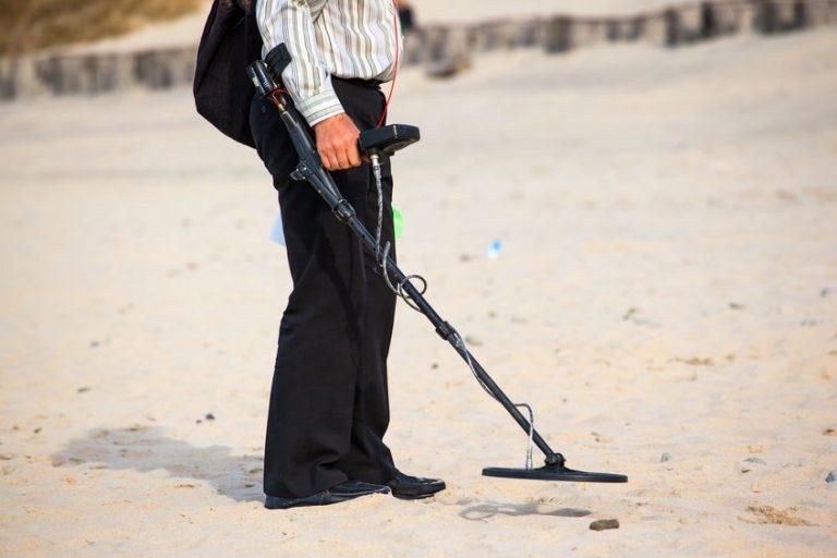 Uomo con il metal detector in spiaggia