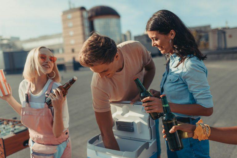 Gruppo di amici che prendono bottiglie da un frigorifero portatile