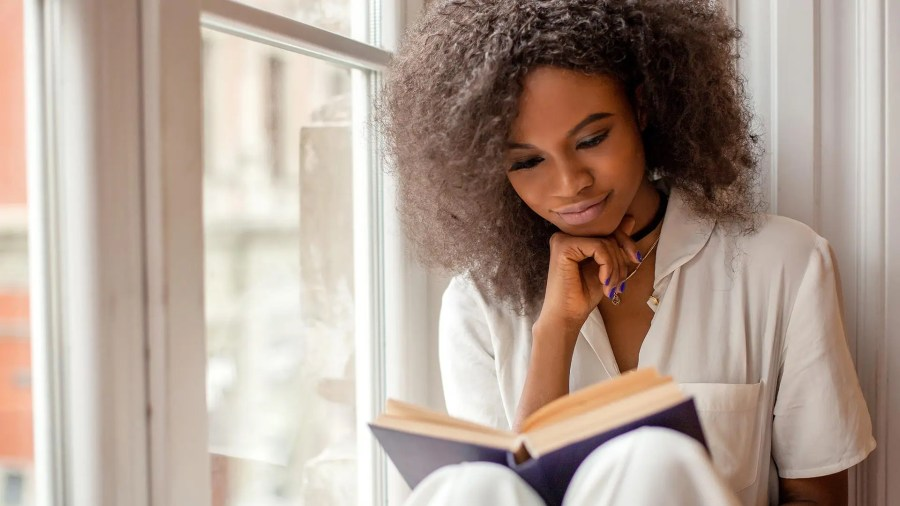 Woman reading a book, sitting on a windowsill