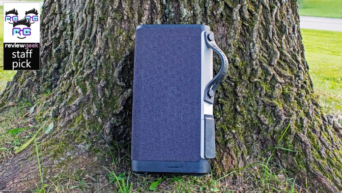 A large portable speaker leaning against a tree.