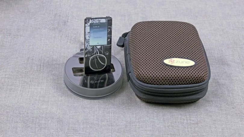 A MIcrosft Zune on a branded dock, next to a Zune branded speaker.