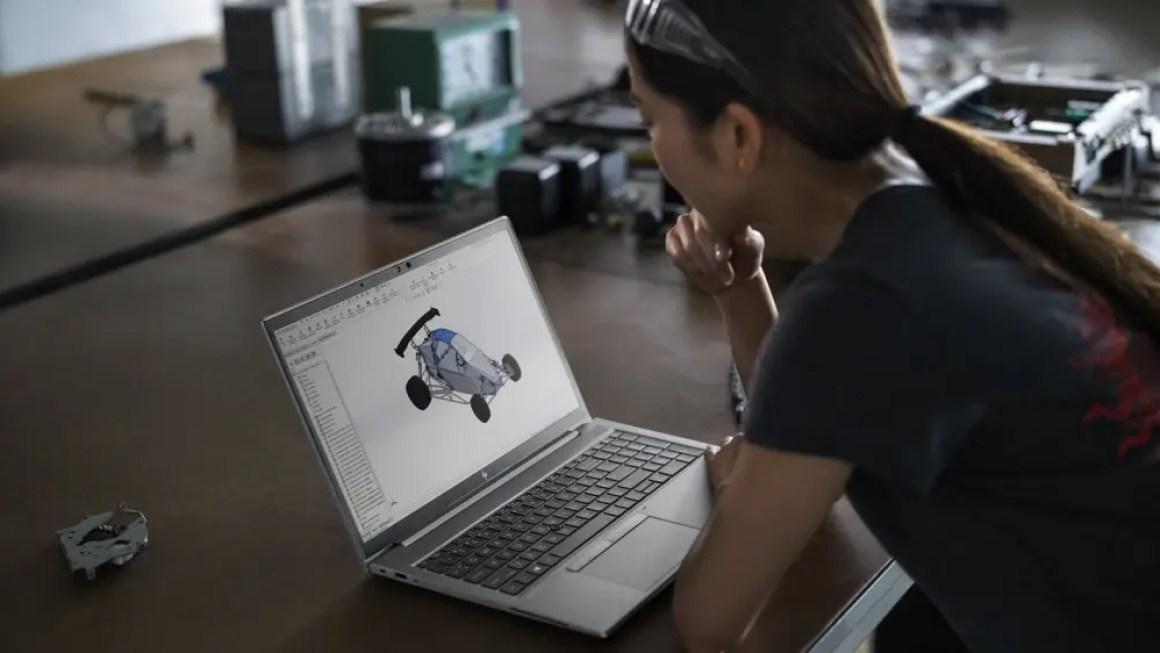 Женщина смотрит на автомобильную схему на ноутбуке HP ZBook Firefly.