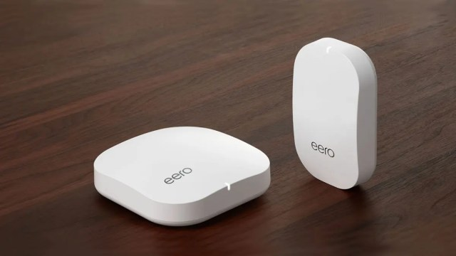 An eero router and a beacon on a wooden floor.