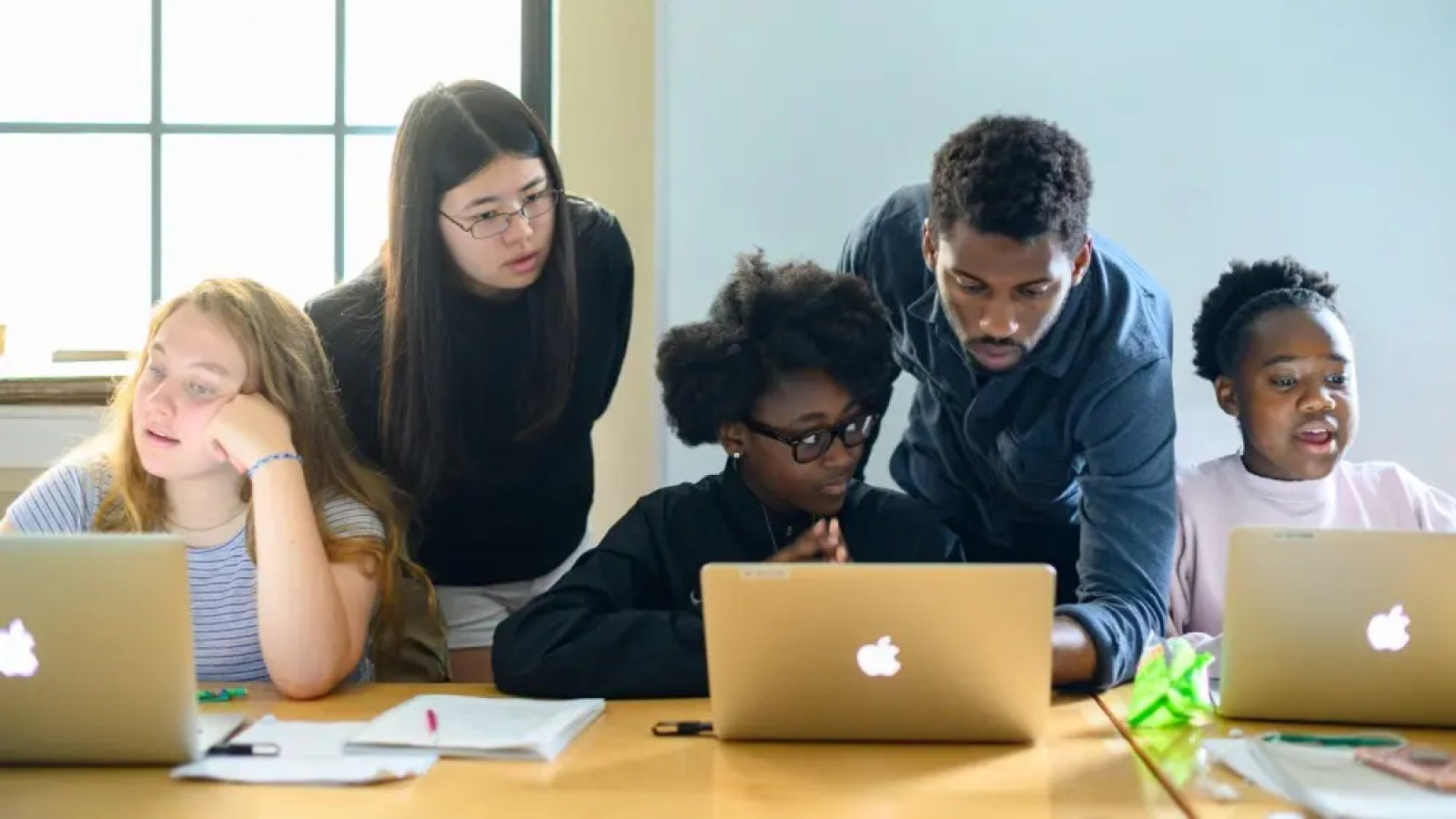 Three young girls learning how to code with two mentors watching over them