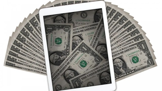 An iPad surrounded by dollar bills