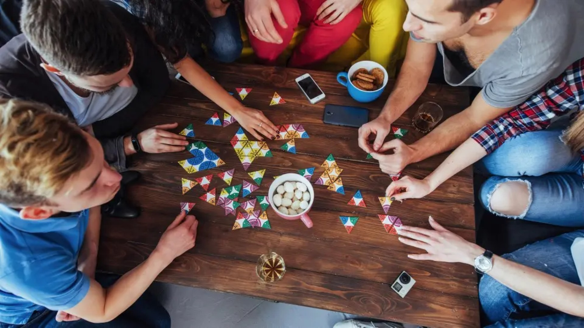 Top view of creative photo of friends sitting at wooden table playing a board game with snacks and drinks
