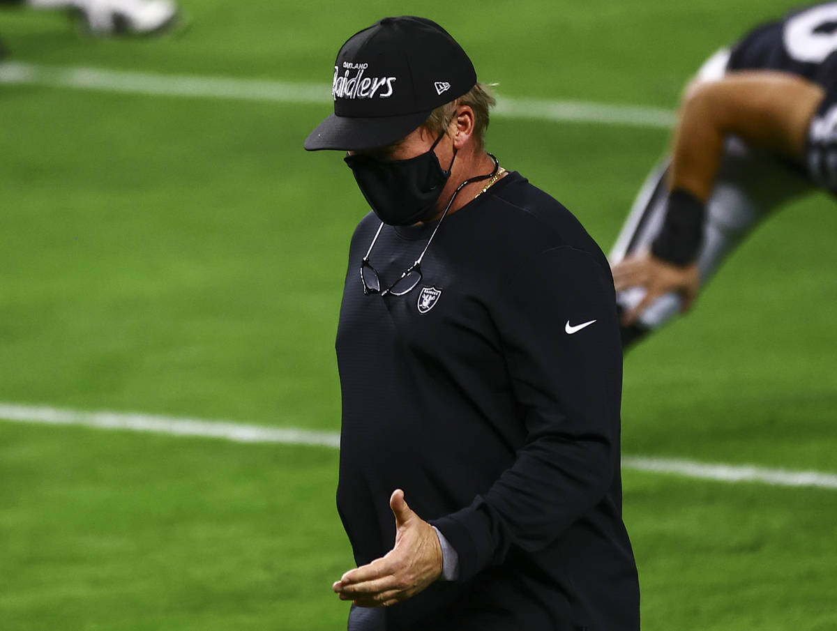 Raiders head coach Jon Gruden, wearing an Oakland Raiders hat, greets players as they stretch b ...