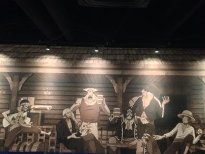 The pirate king crew painted in the wall talking sitting in a circle with Shanks and Buggy arguing from across the room