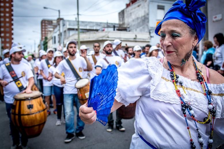 """La figura de la """"Mama Vieja"""" representa la sabiduría y dulzura de las madres y abuelas. Lleva un pañuelo blanco sobre la cabeza, un abanico, un paraguas, un canasto con flores y una pollera grande."""