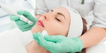 Cosmetóloga realizando inyección de mesoterapia a mujer joven - belleza
