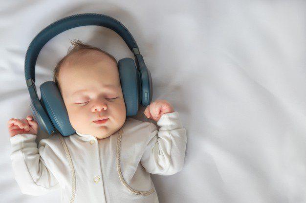 bebe recien nacido sonriendo escuchando musica auriculares acostado sabana blanca cuna infancia feliz despreocupada bebe imagen tonificada vista superior primer plano 262398 206