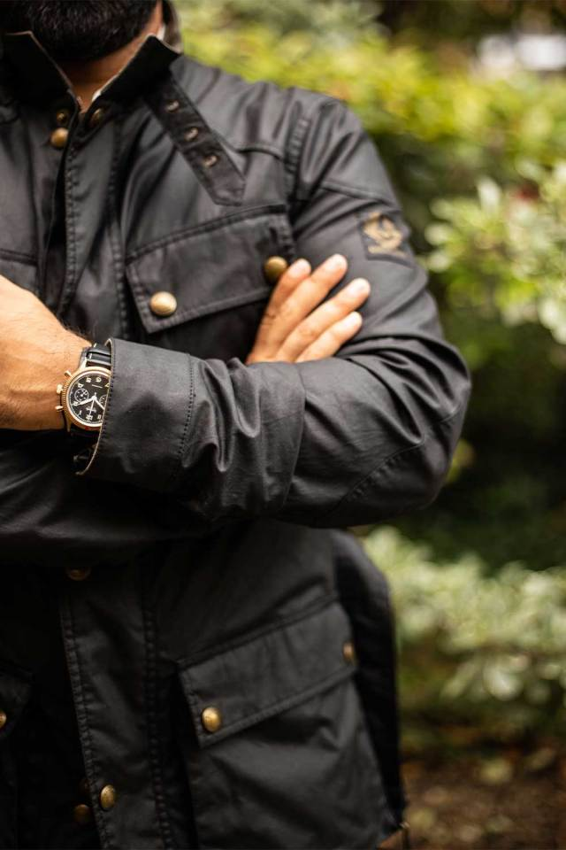 The Hanhart x The Rake & Revolution Limited Edition Bronze 417 Chronograph seen here paired with our exclusive faded vintage black Belstaff jacket completed by its brass snaps and zipper (©Revolution)