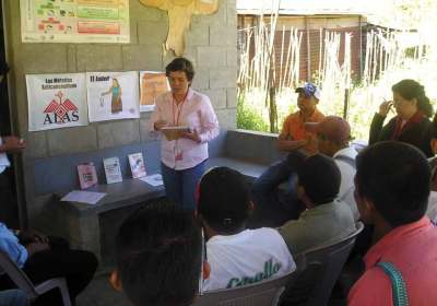 Direct Services Coordinator Patty Medina speaks to men at a community charla in Alta Verapaz.