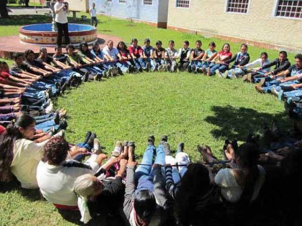 Chicos posando con las manos y los pies en el suelo en un círculo