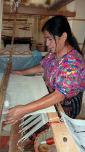 Lidia works on her latest creation using a foot pedal loom