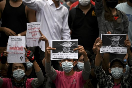 Protesters hold placards during a demonstration against the military coup in Yangon, Feb. 6, 2021. Credit: AFP
