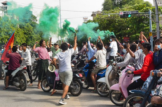 This photo taken and received courtesy of an anonymous source via Facebook shows protesters, some holding flares, taking part in a demonstration against the military coup in Monywa, Sagaing Region, June 21, 2021. HANDOUT / FACEBOOK / AFP