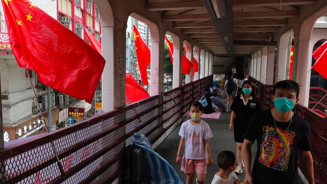 2021 年 7 月 1 日,香港主权移交24周年,居民走过在人行天桥上竖立的中国国旗。 (美联社)