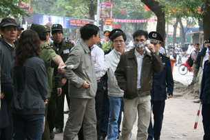Luật sư Lê Quốc Quân đang đứng ôn hòa bên đường phía ngoài khu vực tòa án khi đang xử TS Cù Huy Hà Vũ, thì bị bắt
