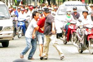 Hình ảnh Chàng trai mặc áo đỏ  tên là Duy, sinh năm 1984, cựu sinh viên trường Kiến Trúc, bị an ninh bắt vì tham gia cuộc biểu tình ngày 12 tháng 6 vừa qua.