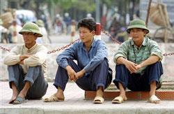 Công nhân thất nghiệp ngồi đợi những công việc mướn làm theo giờ hoặc ngày ở Hà Nội. AFP