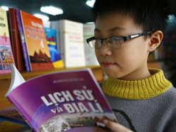 Một học sinh đang xem sách Lịch sử và Địa lý. Photo courtesy of tienphong.vn